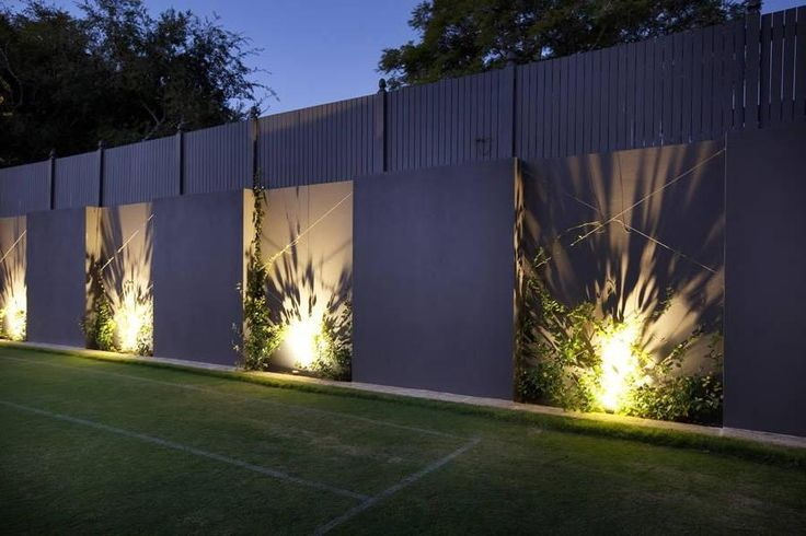 Fascinating high concrete fence design with spotlamps and green plants…