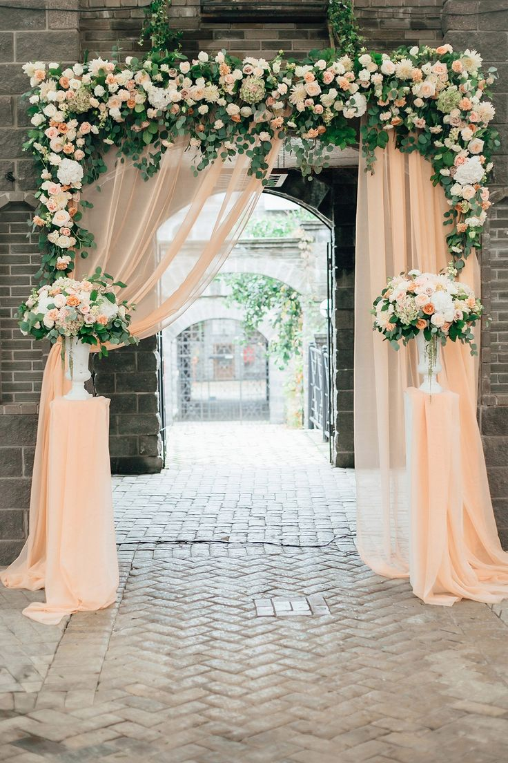 Wedding ceremony Flower arch with a light peach-colored fabric decorated with compositions in high vases on the sides using roses, carnations, hydrangeas, methiol, eucalyptus and salal