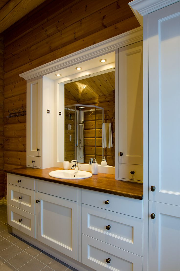 White bathroom-furniture, handcrafted and handpainted, from Os Trekultur. It's fitted to the timber-walls.