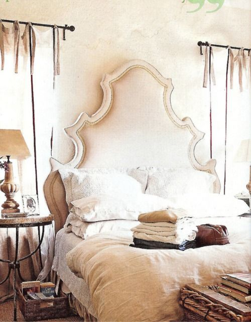 beautiful headboard hanging curtains and large basket at the end of the bed