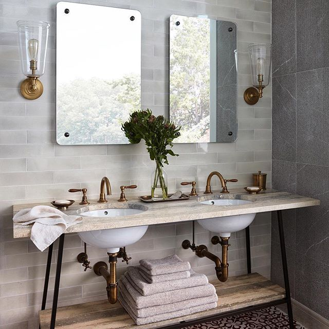 Sharing a bath never looked so good. Our Easton faucets and Henry sconces (in vintage brass finishes) give the earthy space a warm glow. #ThePerfectBath