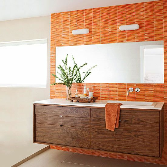 An orange tile accent wall lets the color do the talking in this vibrant bathroom. A large frameless mirror balances the bold hue and adds to the horizontal effect of the space.