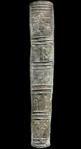 Luristan bronze quiver, 10th-8th century B.C. Iran, narrow convex rectangular shape, slightly tapering towards the end, with holes along the edges for stitching to the leather container now missing, decorated in repoussé and incision, divided into five registers representing at the top a deity in a winged and tailed ring flanked by two adorants, three female figures below, two bearded men facing each other and in the bottom panel a hero battling lion or leopard, 60 cm long. Private…