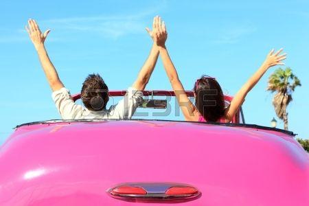 Vrijheid - gelukkig vrij paar in de auto rijden in roze vintage retro auto juichende vreugde wih armen omhoog. Vrienden aan de hand road trip reizen op zomerse dag onder de zon blauwe lucht. Stockfoto