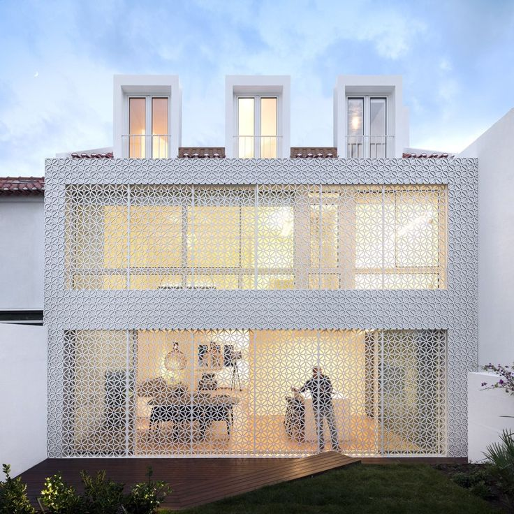 resembling a pattern of traditional portuguese tiles, the rear façade of the dwelling provides residents with privacy, security while filtering sunlight into the interior.