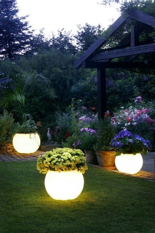 Use glow in the dark paint on existing or new planters - sunlight in day makes them light up at night.