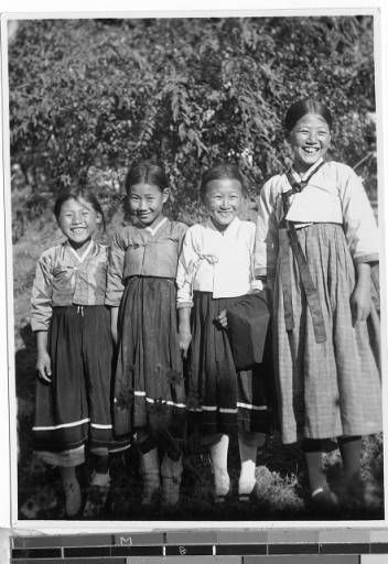 """Smiles are the style here in Korea. Here's a quartet from my little school showing you how to smile. How do you like them? They are four little pagans but are now preparing for baptism. Picture from Fr. Carroll, Masan, Korea"" Photograph of four smiling girls dressed in traditional Korean outfits. The girl second from the right holds an object wrapped in fabric. ca 1920-40"