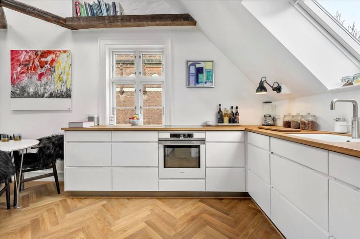 vigas de madera techo inclinado interior abierto encimera de madera decoración nórdica cocina nórdica cocina moderna cocina en forma de L cocina blanca ático dúplex