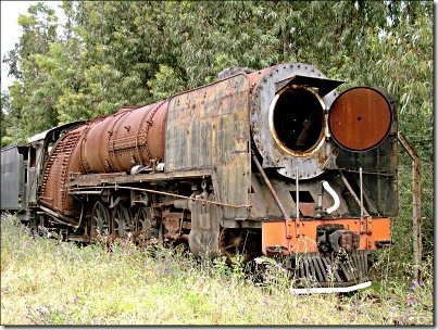 Old steam engine near a repair shed in South Africa