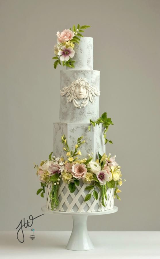 This is my contribution to the March issue of DIY Weddings magazine. The cake was inspired by the elements of a classic garden with strong architectural features and lavish floral motifs. The Bas relief angel, reminiscent of ancient carved key...