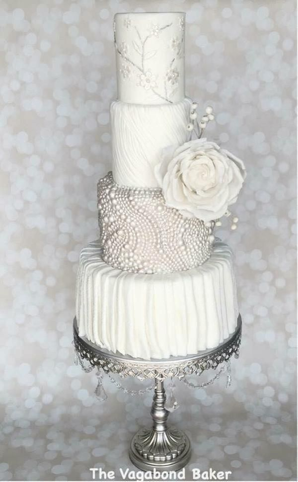 This four tier white wedding cake with pearls and floral detail is simply stunning! - by The Vagabond Baker