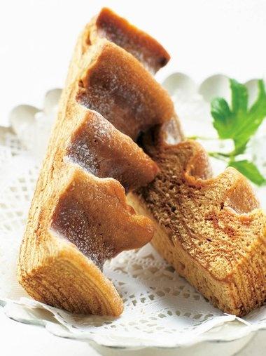 「シェ・タニ」の「黒糖バームクーヘン 山樵」 外はサクッと香ばしく、中はしっとりとレイヤーの入った高級バームクーヘンは、熊本市にある洋菓子専門店「シェ・タニ」の谷誠志シェフによるもの。たっぷりの沖縄産黒砂糖を、通常の2倍の時間をかけて生地に練り込み、低温でじっくりと焼き上げ、シュガーコーティング。独特の凹凸のフォルムに砂糖がけがこっくり絡むのもおいしさのポイント。大きめ食べきりサイズの3本入り。