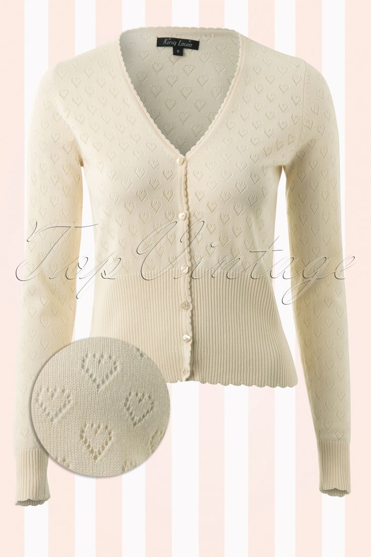 A darling40s Heart Ajour Cardigan in Creamby King Louie!  Love at first sight! When you're wearing this super cute cardi with openwork hearts you won't have to suffer from the cold ánd you'll look fantastic, all at once ;) Made from a supple cotton blend with stretchy, scalloped rib board along the sleeves and bottom for a perfect fit that will not lose its shape. The scalloped V-neck and cute heart shaped buttons finish it off perfectly, musthave! The featured pumps, dres...