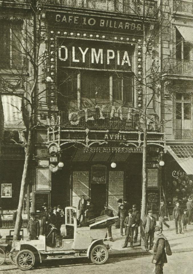 Boulevard des Capucines en avril 1900, l'Olympia est ouvert depuis seulement 7 ans. A cette époque, les acrobates et contorsionnistes sont encore à l'affiche....