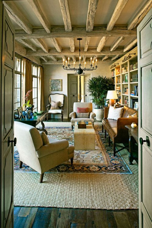 I love this room. rug on rug..wood beams...french windows..bookshelves..love everything..