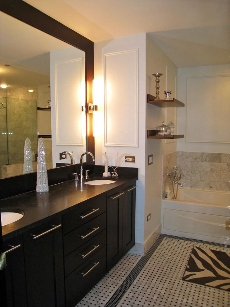 This elegant master bathroom is definitely not short on storage. Narrow wall shelves next to the shower display the owner's fine accessory selection along with miniature, clear storage jars. Ample under-sink storage keeps these solid-wood countertops clear and clean.