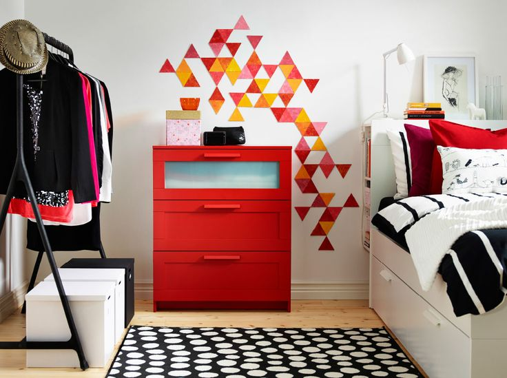 A red chest of 3 drawers standing against a white wall with a geometric pattern in yellow, red, orange and pink.