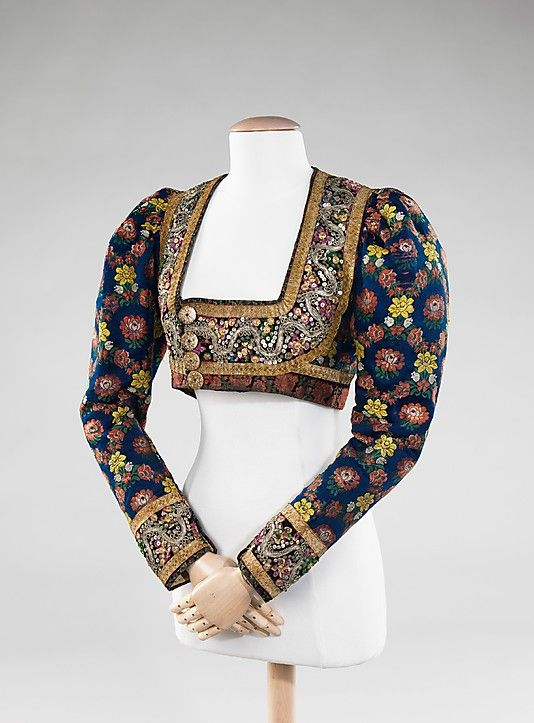 Bodice, Austrian, silk, metal, wool, synthetic, 1890-99. This handsome piece incorporates an interesting combination of materials with lively patterning and embroidery. The puffed sleeves mimic the leg-o-mutton style prevalent in the 1890s. Regional costumes often evolved over time, incorporating fashionable trends with traditional forms.