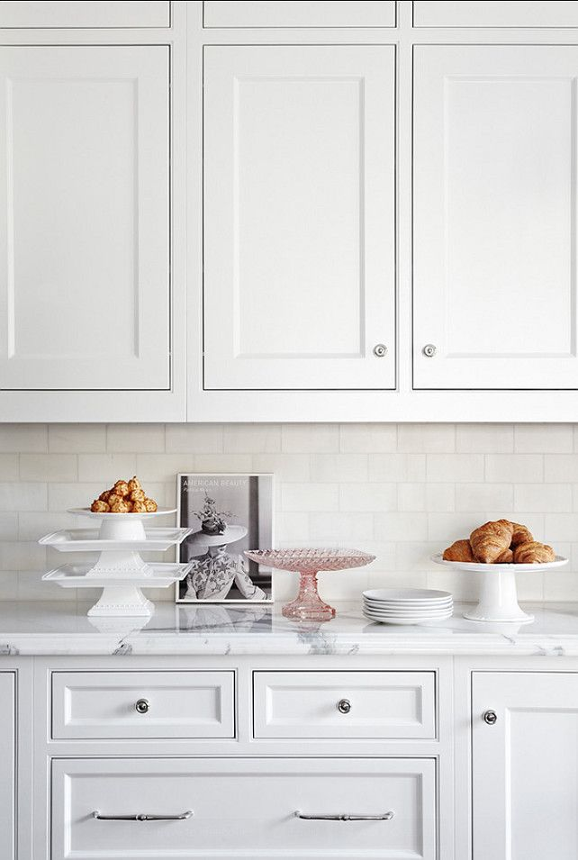 The backsplash in this kitchen is classic white subway tiles and white marble for the countertop.
