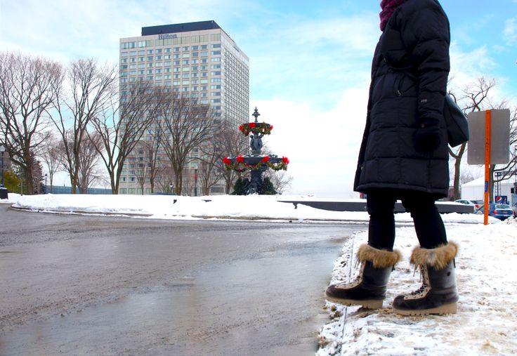 La fontaine de Tourny dans la Ville de Québec, avec l'Hôtel Hilton en arrière-plan. / Quebec City's Tourny Fountain, with Hilton Hotel in background.   Bottes en fourrure de loup-marin et garniture de coyote / Seal and coyote fur boots
