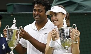 Martina Hingis, right, celebrates her second Wimbledon title in two days with Leander Paes.