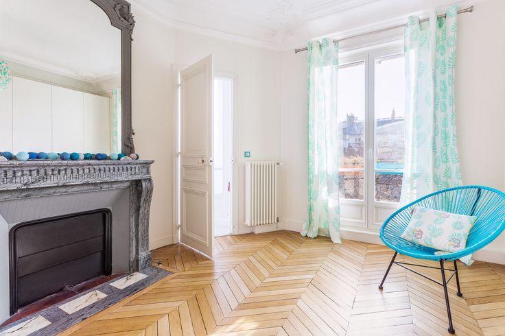 Parquet pointes de Hongrie, cheminée ancienne en contraste avec un fauteuil bleu moderne - décoration par Coralie Vasseur dans un appartement parisien haussmannien