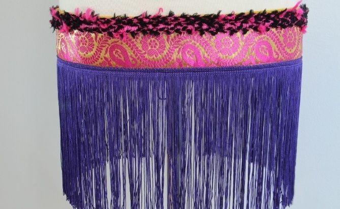 Cinturón con flecos lilas, cenefa oro-fucsia, pasamanería de lana negra y fucsia.