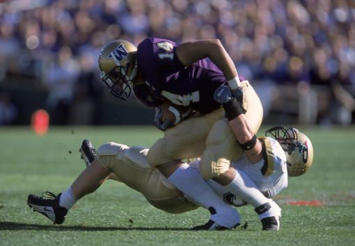 Jerramy Stevens of the Washington Huskies moves with the ball as Joe Odom of the Purdue Boilermakers tries to tackle him during the Rose Bowl Game at...