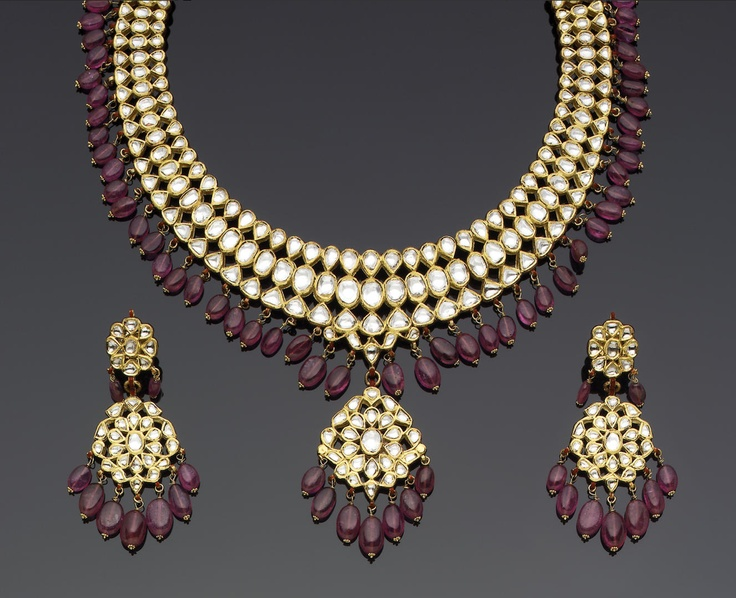 An Indian diamond and tourmaline-set enamelled gold Necklace and Earrings crescentic, composed of openwork floral elements with a central pendant, all with a tourmaline fringe, verso enamelled in polychrome with floral designs; the earrings ensuite 18 cm. diam. approx.