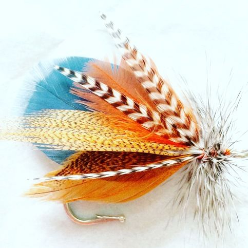 Hand tied fly fishing boutonniere  Style: Fox Run  Colors: Blue, brown, grey, orange, black, white, tan  Size: 2 Tall, 3 Wide  Materials: Feathers  Brooch style pin for easy wear  Custom designs available.  Email BlueSpruceFlyCo@Hotmail.com