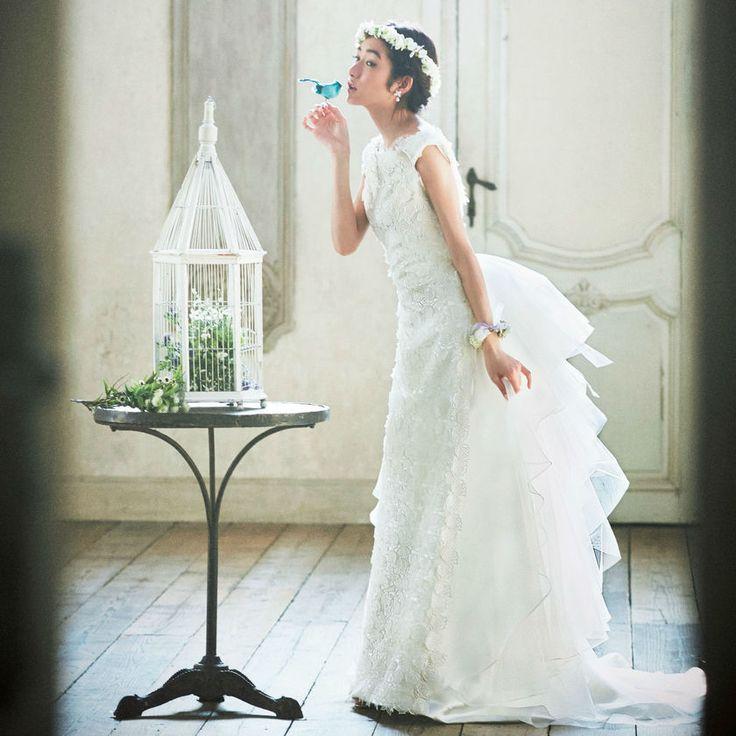 """小柄花嫁ドレス①エアリー素材&レースづかいが魅力の""""シャビー・シック""""  小柄な花嫁が持つ可愛さを引き出すには、張り感のあるドレスよりも、ふんわり軽いエアリーな素材感やレーシーな質感を選ぶのがポイントです。  「セ・ミューJUNKO TAMAI」のドレスは、フロントにリーフをかたどったレースを全面にあしらって、バックはティアード状のチュールがふんわりとなびき、シャビー・シックな雰囲気を醸し出してくれます。  小花でつくられた花冠と腕輪をつければ、まるで童話の世界のプリンセスに。まさしく小柄花嫁の特権とも言えるデザインですね。"""