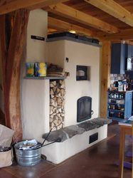 Masonry heater with pizza oven above and cob as the thermal mass. Lovely timber-frame and earthen floor, to boot.