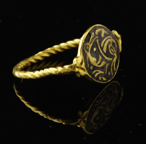 Extremely rare gold saxon ring with a flat circular bezel engraved with a champlevé zoomorphic pattern inlaid with black niello; the hoop is formed by a single wire twisted like a torque, a typical early saxon design, the shoulders terminating in foliate motifs. The original niello is restored and protected by a varnish (who the hell would do that?...).  Northumbria probably late 9th.