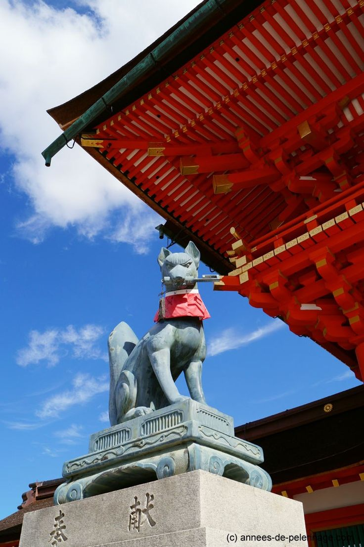 A bronce fox statue with a tool to harvest rice at fushimi inari taisha shrine in Kyoto, Japan