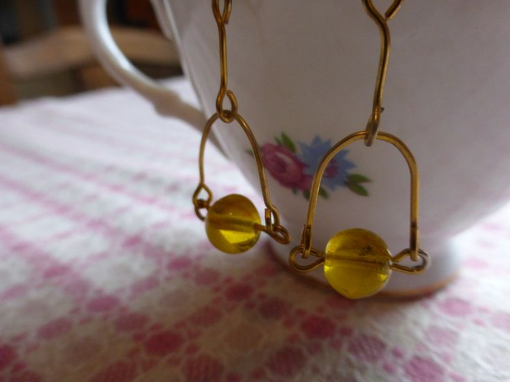 Earring: yellow bead swinging on gold wire by TheCatAndTheClasp on Etsy