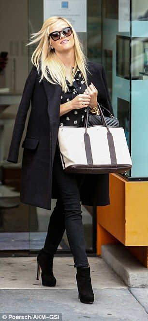 Fashionable star:Witherspoon was dressed mostly in black, with a knee-length trench coat draped over her shoulders