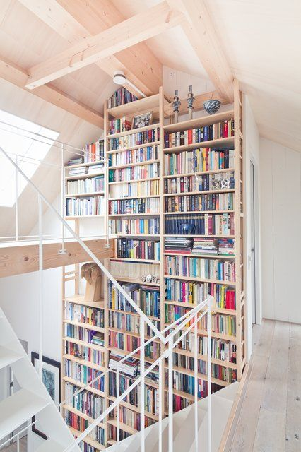 book shelves, looks like floor to ceiling in a loft