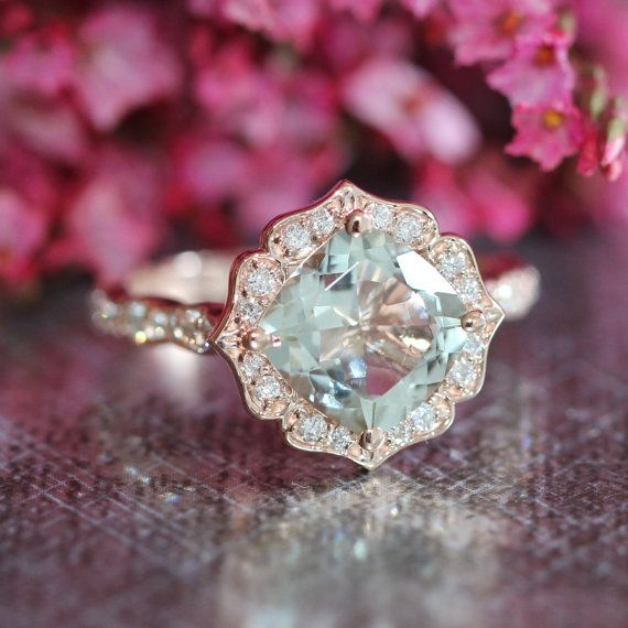 This vintage inspired engagement ring features a 8x8mm cushion cut natural light green amethyst set in a solid 14k rose gold floral diamond setting