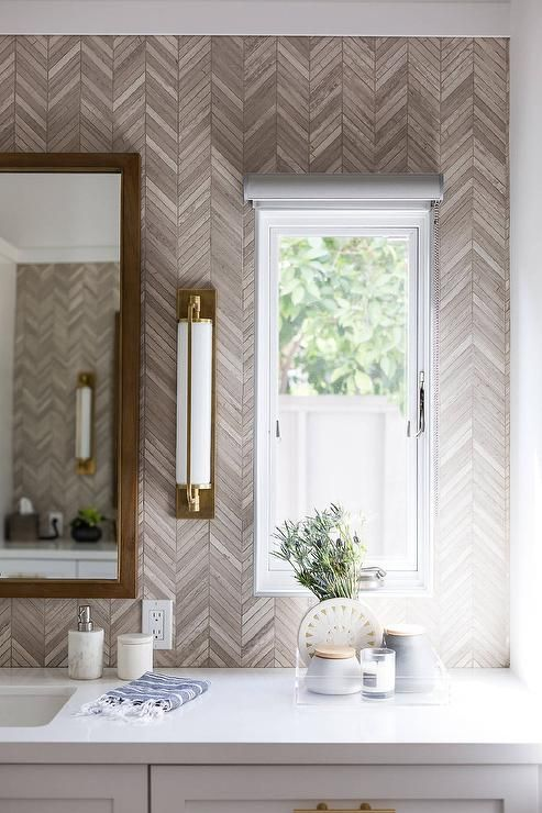 Gray and gold bathroom features a wood framed vanity mirror fixed on taupe herringbone tiles beside a Keeley Tall Pivoting Sconce mounted next to a window covered with a white rolling shade and located above a light gray washstand topped with a white quartz countertop.