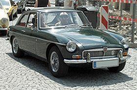 """El techo fijo MGB GT se introdujo en octubre de 1965. La producción continuó hasta 1980, aunque la exportación a los EE.UU. cesó en 1974. El MGB GT lucía un innovador efecto invernadero diseñado por Pininfarina y lanzó el deportivo """" ventana trasera de estilo"""". Mediante la combinación de la luneta trasera inclinada con la tapa de la cubierta trasera, el B GT ofreció la utilidad de una camioneta al tiempo que conserva el estilo y la forma de un coupé. Esta nueva configuración se ha realizado…"""