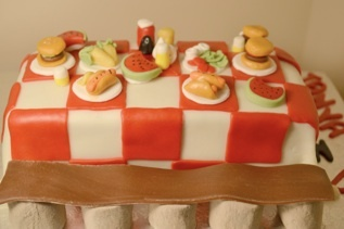 Pink Piggy Sweets® picnic themed cake sweet using fondant for icing and food accents.  Marshmallows used for bench.