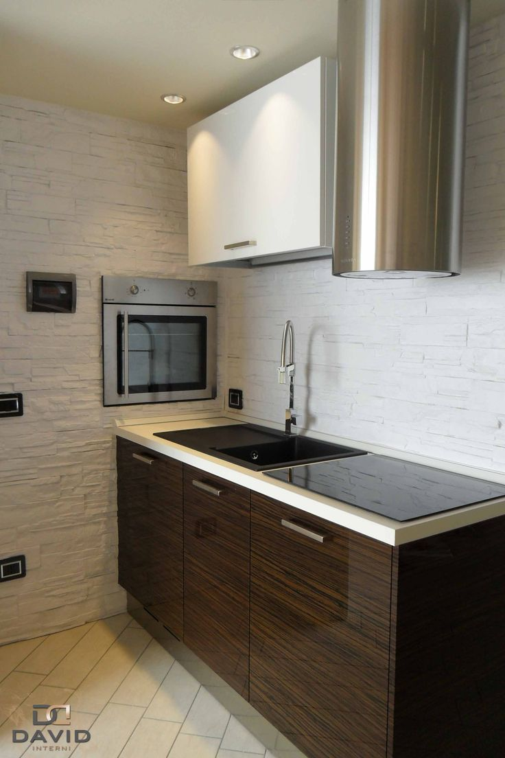 Cucina su misura in laccato bianco e ebano con elettrodomestici in acciaio inox e forno incassato nella parete