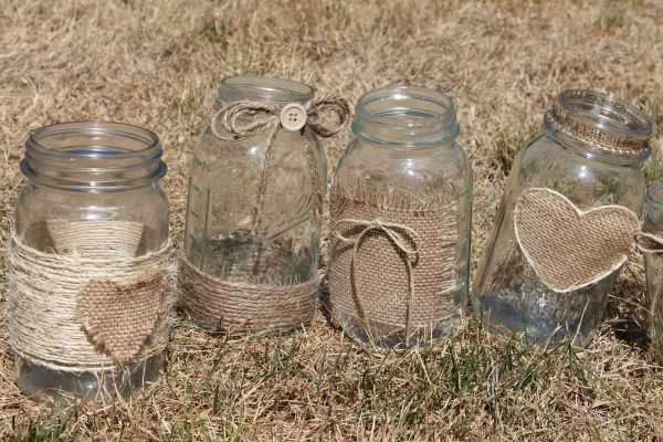 Hessian and string decorated jam jars. Great for flowers or candles on the wedding table.