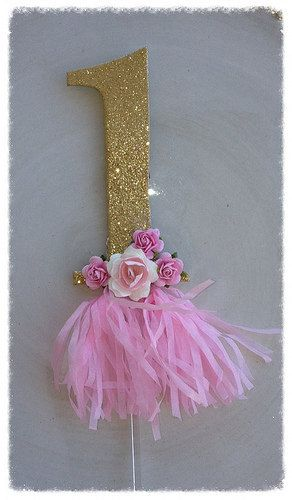 A very cool gold glittered number has a sweet pink tissue paper tassel. Number is glittered on both sides and has a clear pick. Paper roses have been