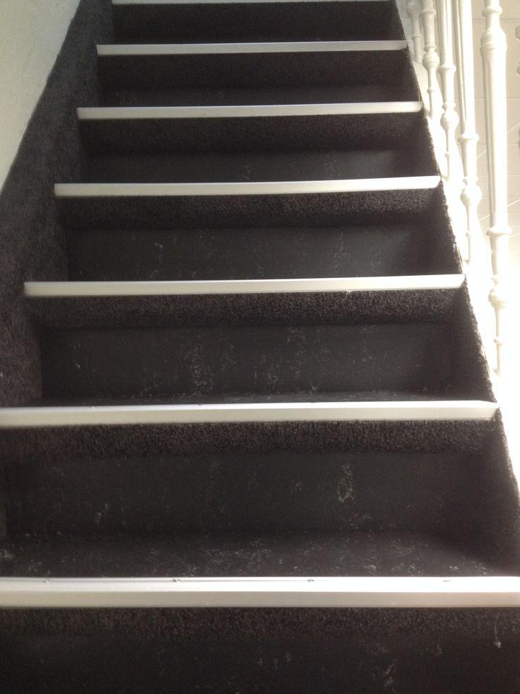 Trap met gemarmerd marmoleum op de treden en tapijt op de stootborden