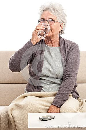 Old woman with a blanket on knees drinking glass of water. Senior woman sick. Isolated on white.