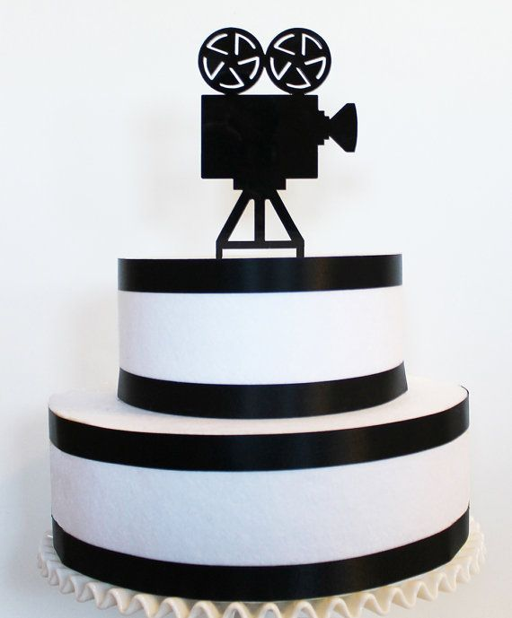 """Laser cut acrylic movie camera cake topper made from 1/8 black acrylic. Perfect for your movie themed wedding or event. Measures 4.5"""" inches wide x 8.25"""" inches tall including stakes Stakes are 2 inches tall  Laser cut from 1/8 inch black acrylic.  *Custom made cake toppers are available - contact us for pricing*  Proudly made in the USA at the Tiffzippy Designs studio."""