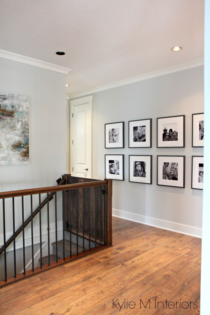 Benjamin Moore Gray Owl one of the best gray paint colours for a dark hallway or staircase by Kylie M Interiors. With photo gallery wall of kids and dark wood and metal stair railing