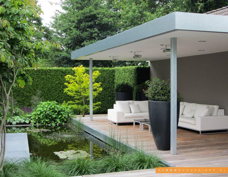 Tuin idee De Rooy Hoveniers strakke tuin overkapping loungeset vijver beplanting Waalwijk