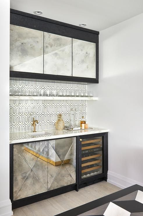 Chic contemporary black and white wet bar is fitted with antiqued mirrored cabinets positioned beside a glass front mini wine cooler and beneath a white marble countertop finished with a small sink with a brushed gold faucet.
